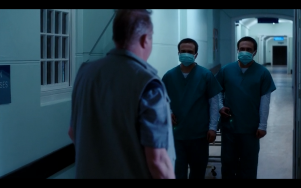 Two doctors in masks face Brian in an empty hallway