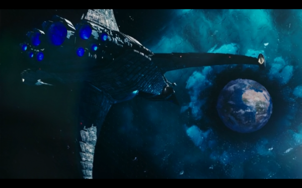Large spaceship pointed at Earth, which is surrounded by a weird blue aura.