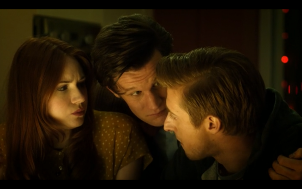 The Doctor leans down between a seated Amy and Rory