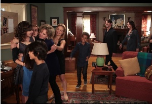 Several family members hug Haddie all at once while others look on.