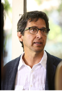 Ray Romano as Hank, wearing a white button-down shirt and glasses