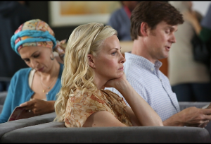 Adam and Kristina sit on a couch in a doctor's waiting room. A woman wearing a scarf tied around her head sits behind them.