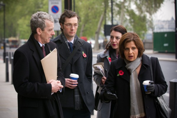 Two men and two women in business attire and coats walking down a street