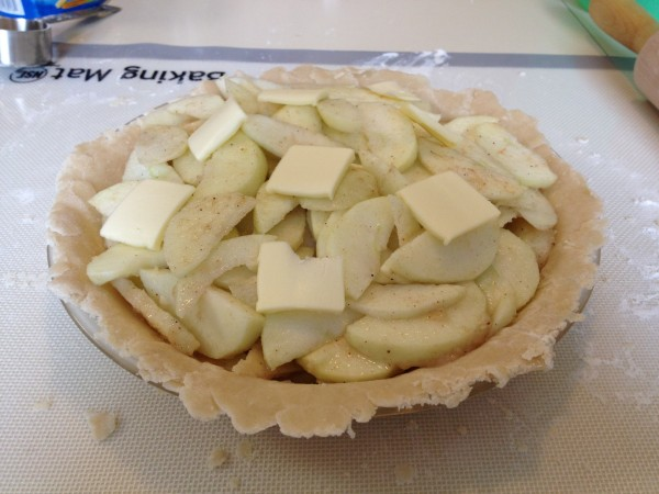 Pie crust filled with sliced, sugared apples, with pats of butter scattered around the top.