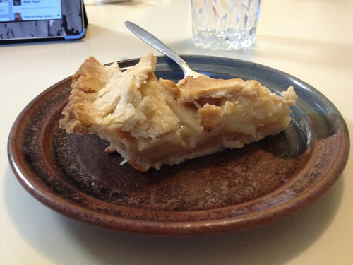 Slice of apple pie on a pottery plate