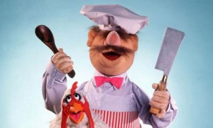 The Swedish Chef muppet holding a wooden spoon and meat cleaver over a chicken muppet