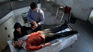 Rhys laid out on the autopsy table, with Gwen kneeling beside him and Jack washing her hand