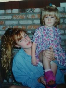 young teenage Kym holding little sister Emily. Kym's hair is just a disaster area. And a denim oversized shirt. It's just all bad. All bad.