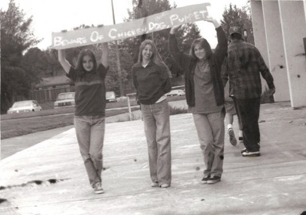"""black and white photo of three teenage girls in jeans and t shirts holding a banner that reads """"Beware of Chicken, Dog, Puppet"""""""