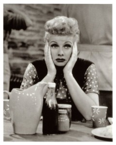 Lucille Ball sitting at a table with her hands on either side of her face