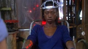 Beth with a sort of metal helmet on her head and her right arm glowing red from within