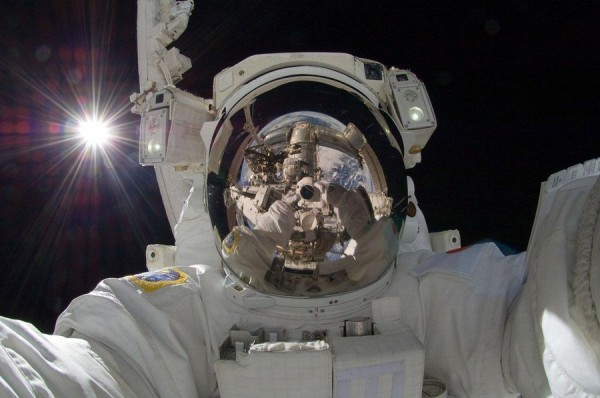 Astronaut in space with the sun behind him and his camera, the International Space Station, and Earth reflected in his visor
