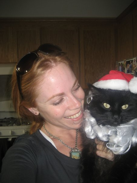 Kym holding Spike, a black cat, wearing a santa beard and hat