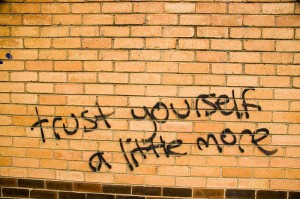 """Trust yourself a little more"" graffiti on brick wall"