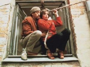 Hines and Rossellini crouched in a window frame. She's roped into an improvised zipline.