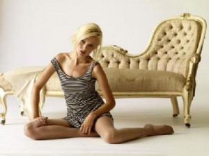 Woman sitting awkwardly on floor in front of a couch