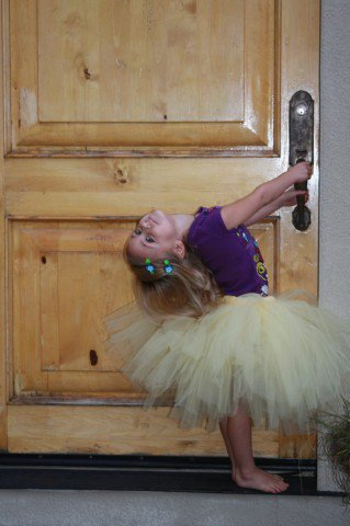 young blond girl in yellow tutu and purple shirt hanging off a doorknob leaning backwards