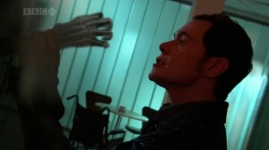 Owen wrestles with Death; a skeleton hand reaches toward his face