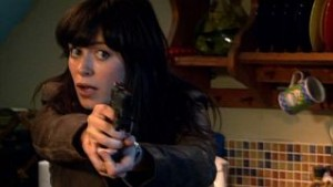 Gwen in her flat, holding her gun out and looking scared