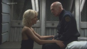 Tigh sits on the edge of a bed. Caprica kneels in front of him with her hands on his legs.