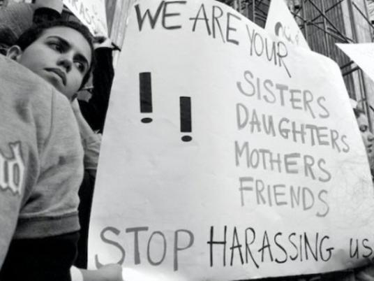 "Closeup of a poster reading ""We are your sisters, daughters, mothers, friends. Stop harassing us!"""