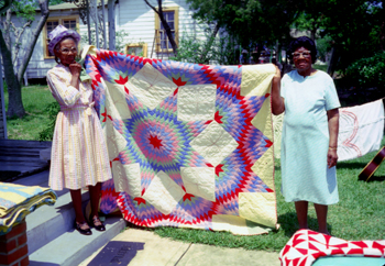 Two African-American women holding up an intricate broken star pattern quilt