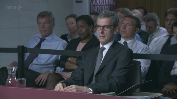 Malcolm Tucker sitting at a witness table with an audience behind him