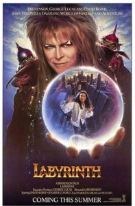 Poster for Labyrinth, showing David Bowie as the Goblin King holding a crystal ball in which we can see Jennifer Connelly as Sarah