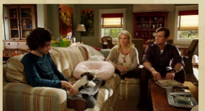 Max sits sullenly on one couch while Adam and Kristina sit on the other