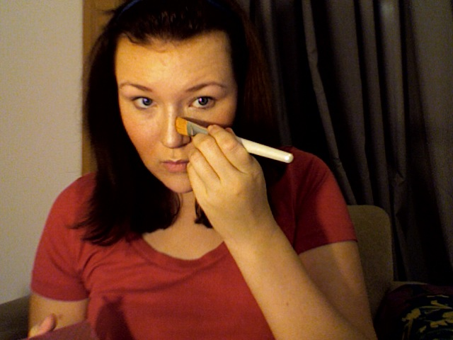 Step 4: Maggie applying bronzer to the sides of her nose with a thin, flat brush