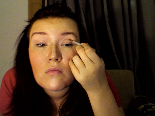 Step 6: Maggie adding a thin line of dark shadow to create a crease in her eyelid