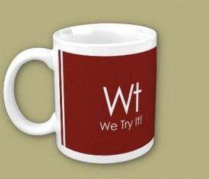 """White mug with red label reads """"Wt We Try It!"""""""