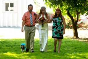 Kym, mom, dad and yorkie/maltese Lola walking down the aisle at Kym's wedding, green grass, tree to the left, ugly ass metal building in the background