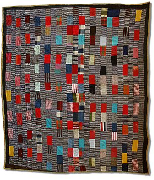 quilt with irregular multi-colored rectangles on a black and white striped background