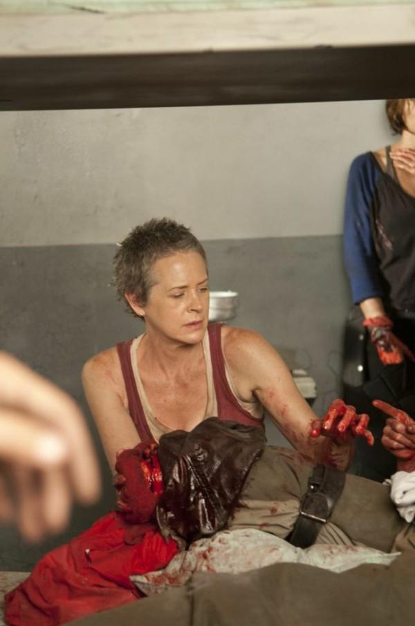 Carol kneels next to Herschel's bloody stump of a leg