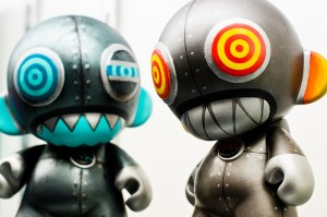 Custom Munnys, silver, large-headed figurines with decorated eyes, ears, and mouths