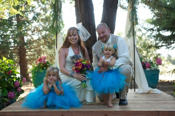 wedding photo on wood platform among redwood trees; Kym in wedding dress holding dog, Jon in tan vest and white shirt holding Charlie, blond little girl in teal tutu and white tank top; Sierra, blond little girl, in teal tutu and white tank top sitting with chin in hands