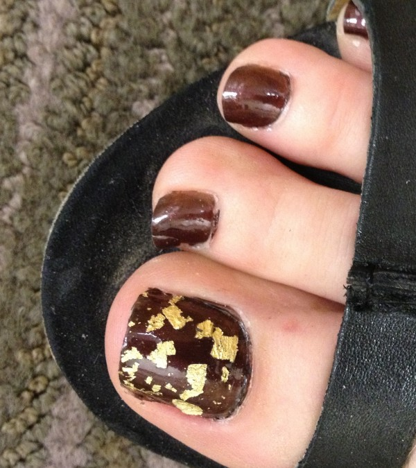 Kym's toes painted dark brown with gold flecks on the big toe. Note- Kym's toes are pretty ugly