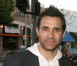 Adrian Paul 2009, with hair slicked up and wearing a jacket over a white hoodie