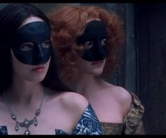 Two women in period costumes, wearing black masks