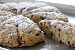 A circle of chocolate chip scones with one scooted slightly out to show the chocolate chips inside.