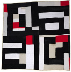 Quilt with irregular rectangles in black, white, red, and tan
