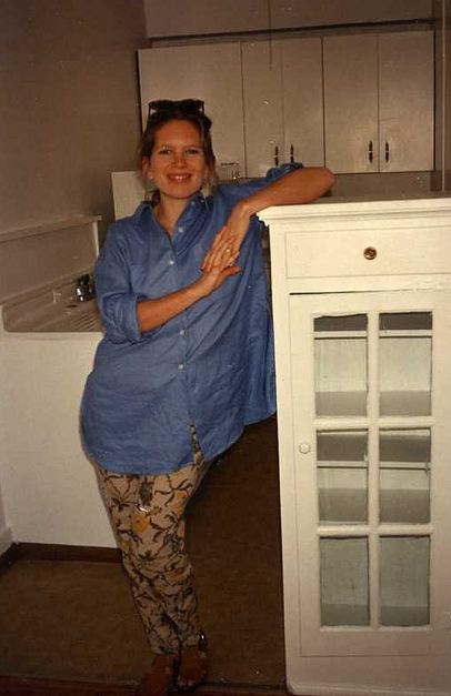 Young woman leaning against a cabinet with glass doors