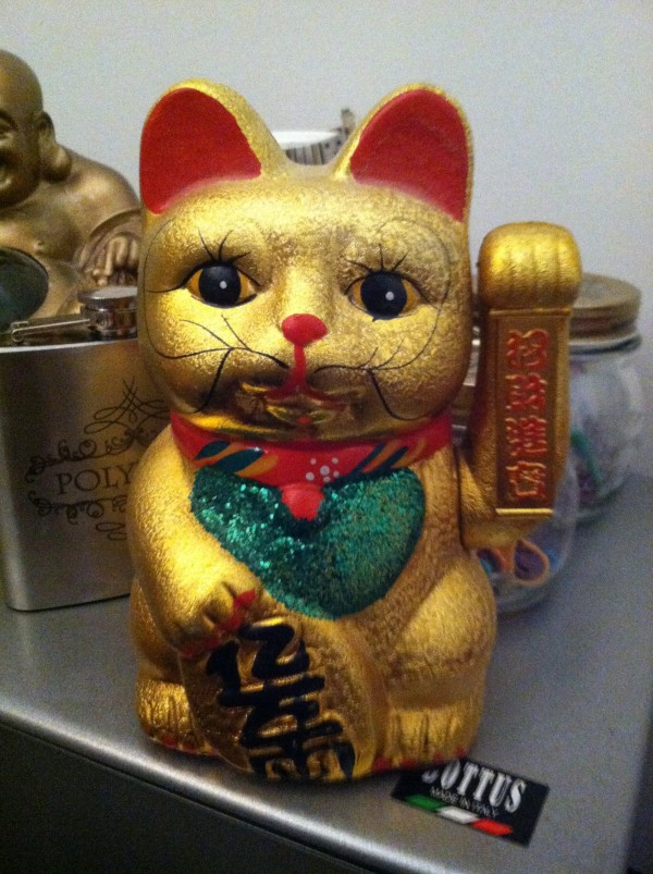 Photo of a waving cat souvenir with one arm raised (that is supposed to wave up and down, but doesn't)