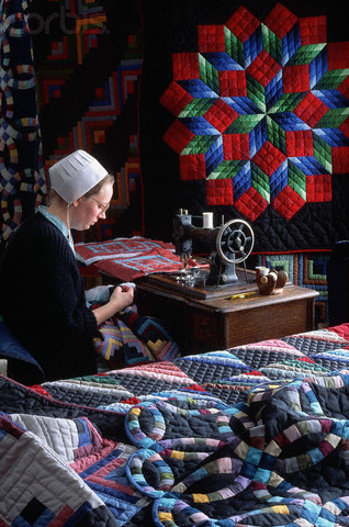 Amish woman seated at a hand-operated sewing machine, with quilts on the wall behind her and the surface next to her