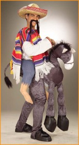light-skinned man in a costume of a poncho-clad man riding a burro, with a sombrero and a long fake moustache.