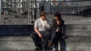 Rhys, with his arm in a sling, and Gwen sit outside the Hub
