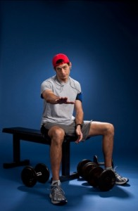 Paul Ryan, wearing workout shorts, a t-shirt, and a backwards red baseball cap, sitting on a weight bench and holding is hand out flat.