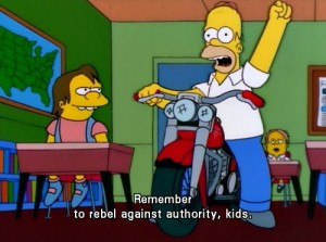 "Screencap from the Simpsons of Homer sitting on a motorcycle in a classroom saying ""Remember to rebel against authority, kids."""