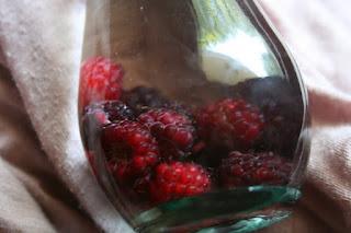 Closeup of lack raspberries in a clear bottle of vodka